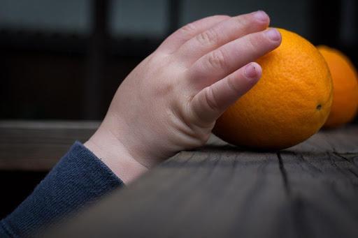 child grabbing orange